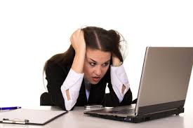 Woman under pressure, head in hands working at her laptop