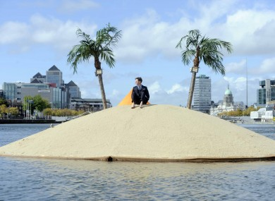 Man on a desert island in city harbour
